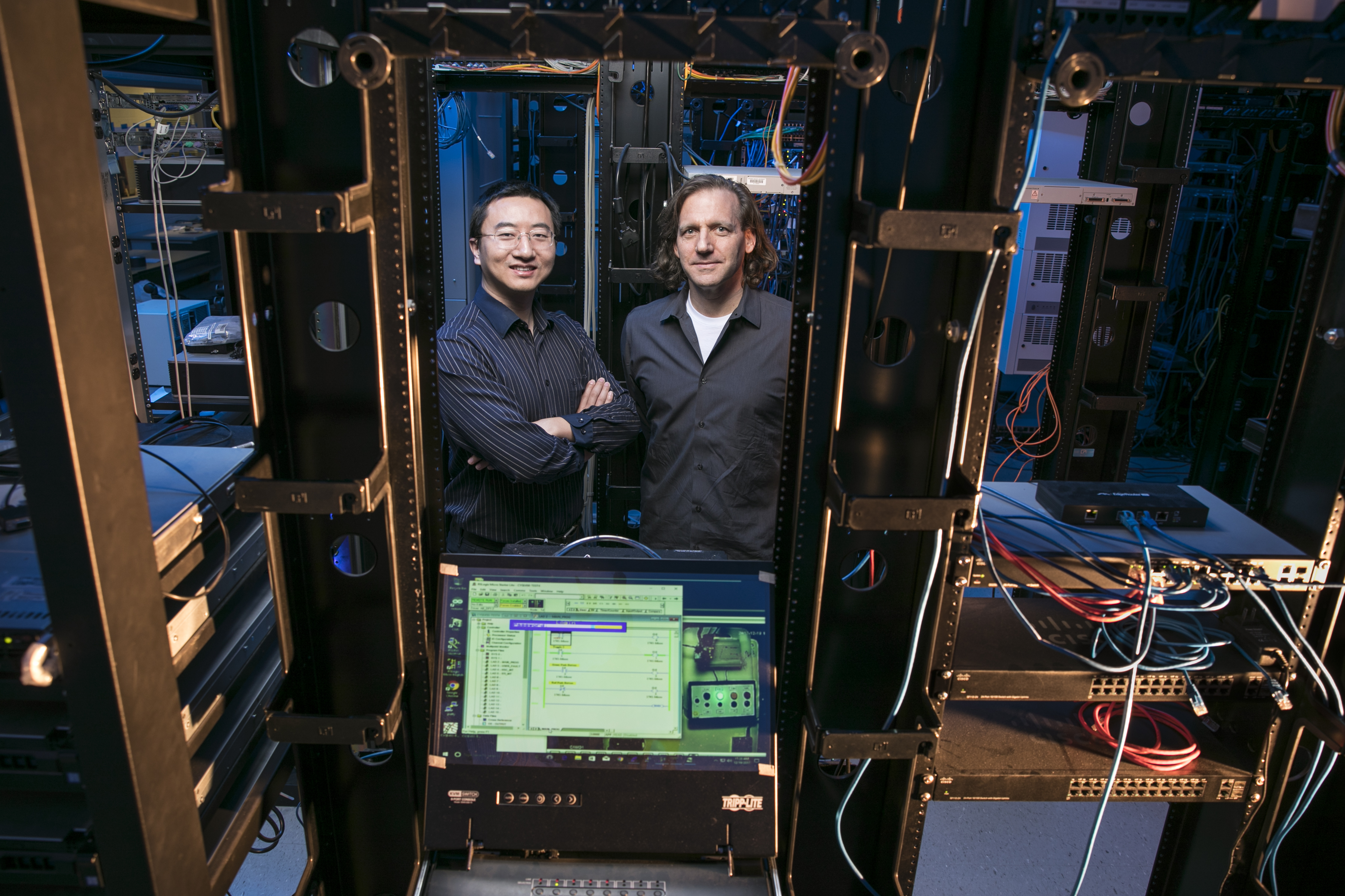 Professors Kai Zeng (left) and Jim Jones work together in the cyber-physical security lab. Photo by Ron Aira.