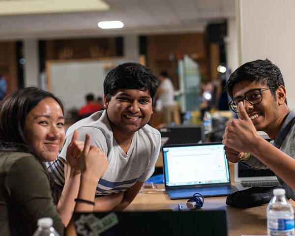 Students smile and give thumbs up during Patriot Hackathon, Pictured: three people, computer, desk
